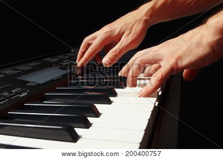Hands of pianist playing the electronic organ on a black background