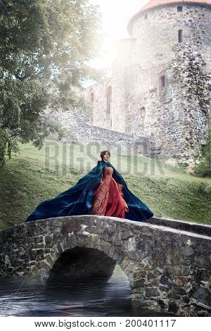 Beautiful Isabella of France queen of England on Middle Ages period in red gown near medieval castle