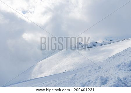 Beautiful mountains white snow and skiers high in the mountains in Sochi Russia
