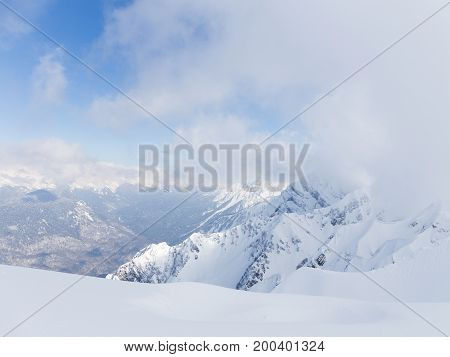 High mountains lots of white snow and clouds lie on the mountains in Sochi Russia