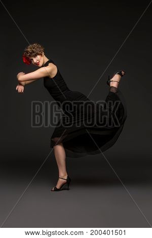 beautiful young woman dancer in tango dress with rose in hair on black background. copy space.