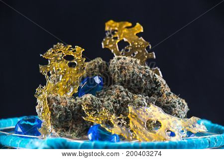 Macro detail of cannabis nugs and marijuana concentrates (aka shatter) with smoke isolated over black