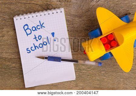 Open white notepad with inscription BACK TO SCHOOL with helium pen and yellow toy airplane on the old wooden table