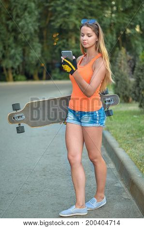 Young and beautiful girl is holding her skateboard in her hands and looking at something on the phone