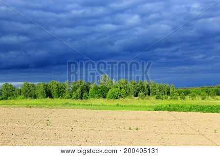 landscape with dark thundercloud clouds under the forest and land. The sky before rain