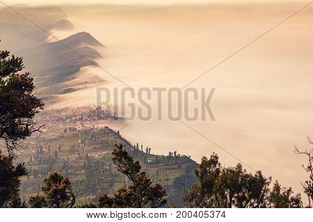 Landscape of Cliff and Cemoro Lawang village in high angle view with sea mist at Mount Bromo volcano in Bromo tengger semeru national park East Java Indonesia (Vintage tone filters)