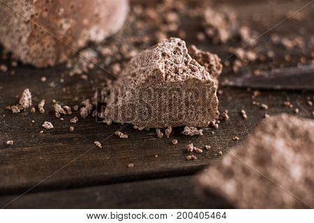 Broken off pieces of aerated chocolate on wooden table. Process of making delicious desserts in restaurant, culinary art close up picture
