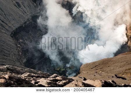 Crater of Bromo volcano (gunung) close-up with erupting smoke in Bromo Tengger Semeru National Park East Java Indonesia