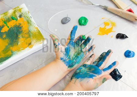 Early childhood education. Dirty little painter. Artist workplace, creative hobby for children, messy artistic background