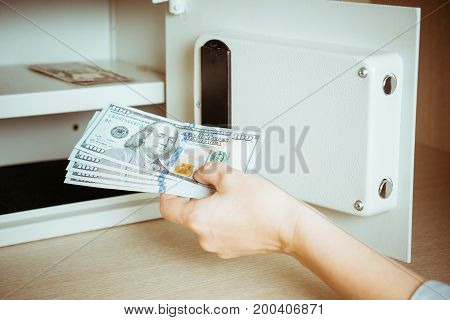 Woman Placing Cash In Safety Deposit Box In Hotel Vault