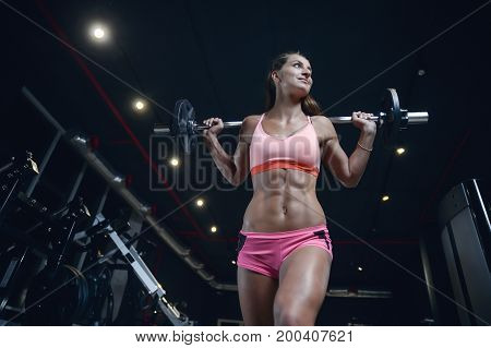 Athletic Young Woman Posing And Exercising Fitness Workout With Weights In Gym