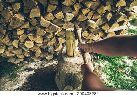 chopping wood first person view, man's hand hold the ax