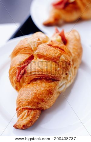 Fresh Croissants on the white plate. Selective focus