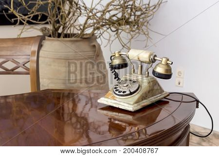 Old, stone phone is on the table close-up