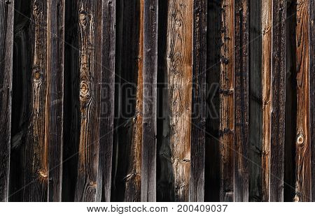 The texture the new dark wooden boards on the boards with brown spots and bulges. Horizontal photo wallpaper