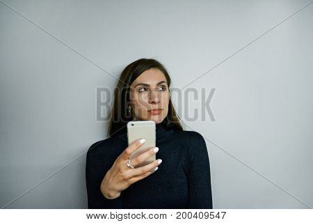 Attractive confident brunette woman wearing black turtle neck using messengers or browsing web sites on mobile phone posing isolated against blank grey wall background with copy space for your text