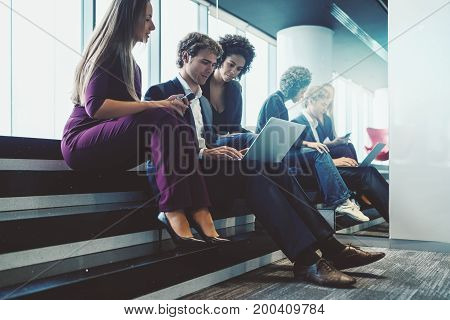Group of three business persons (two women of different races and one caucasian man) sitting on reflective steps of office meeting area stairway and having work conversation using laptop and gadgets