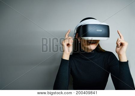 Picture of fascinated excited young brunette female wearing virtual reality modern glasses with head mounted display entertaining herself playing video games or watching something amazing