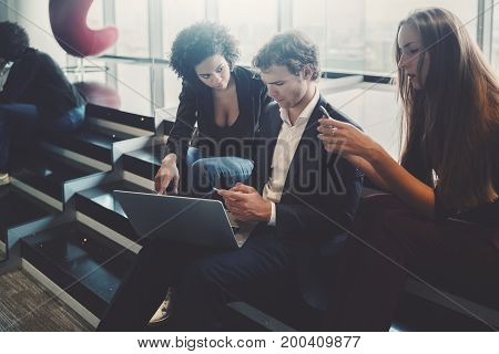 Three business persons are sitting on steps of staircase during work meeting: caucasian woman using smartphone man with laptop and cellphone young black curly girl showing on screen of this net-book