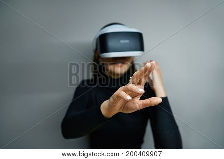 Amazed girl opening mouth in excitement and fascination and reaching out her right arm gesturing while interacting with something experiencing virtual reality in goggles. Selective focus on hand