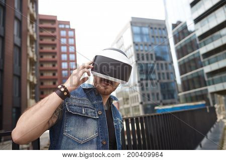 Augmented reality modern 3d technology future and cyberspace concept. Outdoor shot of unshaven stylish young male wearing jeans vest and bracelets standing in urban setting using vr glasses