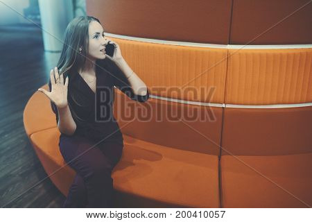 Beautiful caucasian businesswoman having emotional conversation via cellphone with her friend while sitting on orange sofa in office chill out place with copy space zone for logo message or advert