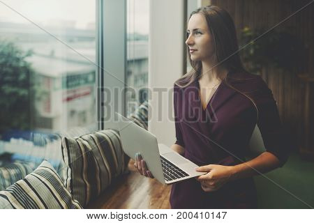 Business lady in purple suit is standing in office settings next to window of chill out area holding laptop and looking outside with copy space zone for advert message or your logo