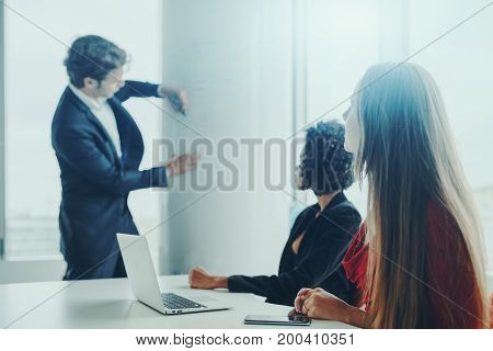 Man entrepreneur in blurred background is using white column in meeting room to write develop plan on it with green highlighter two of his female co-workers with their gadgets sitting in foreground