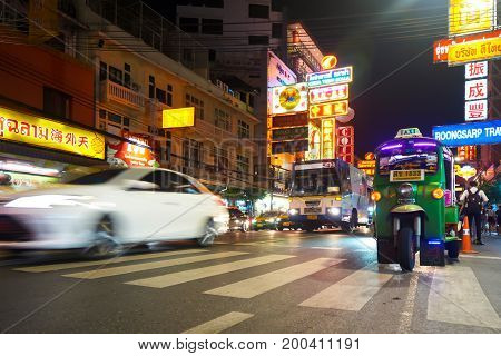Bangkok Thailand - 21 July 2017: Tourist People in night life and Tuk-Tuks (Thai taxi) on the Yarowat Road with transport movement in urban spaces and the building and village of Chinatown at night Bangkok Thailand.