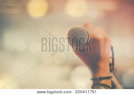 hand holding microphone and bokeh background concept as music instrument in studio room and meeting hall