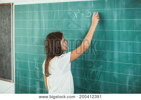 Happy school child writing on blackboard in classroom