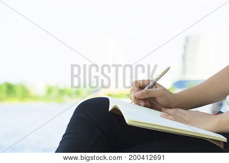 hand of people student writing and note on notebook in park concept as education attempt and make effort to win intend to improve knowledge for future life