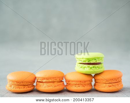 Green color macaroon stand over assortment of orange color macaroon with copy space on bare cement or concrete wall background