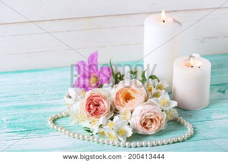 Sweet pastel roses jasmine flowers and burning candles on turquoise wooden background. Selective focus.