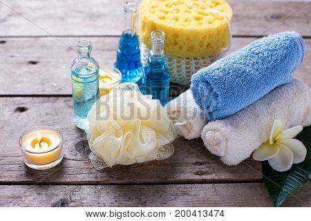 Spa setting in blue yellow and white colors. Bottles wih essential aroma oil towels candles and wispes on wooden background. Selective focus.