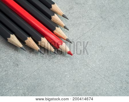 Red pencil standout from black pencil bare cement or concrete wall background leadership business concept