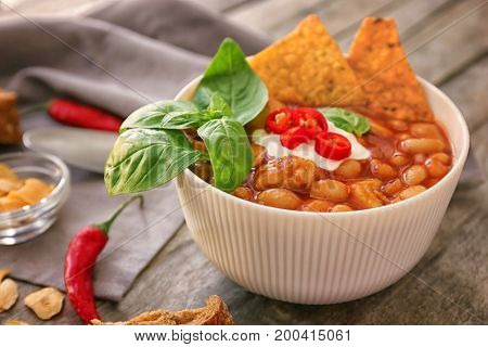 Delicious turkey chili in bowl on wooden table