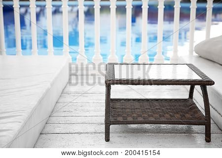 Rattan table near swimming pool in luxury hotel