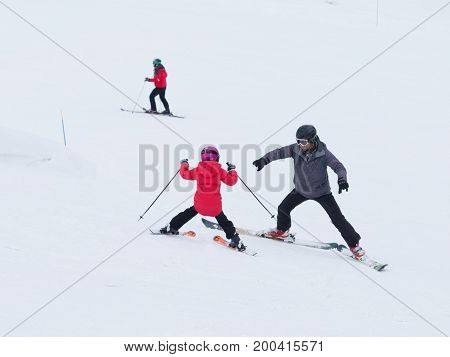 Sochi - March 28 2017: Young children in mountain skiing learn to ski with a coach in gray uniforms in the mountains March 28 2017 Sochi Russia