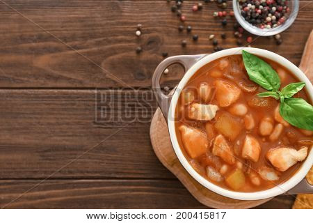 Casserole with delicious turkey chili on wooden table