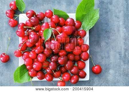 Plate with fresh ripe cherries on grey background
