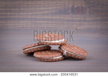 Biscuits with sweet filling on a wooden background.