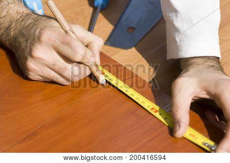 Marking distances. The carpenter's hands measure distance measure.