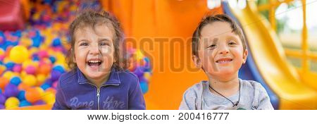 Adorable two smiling little girls and boy. Portrait. Happy children playing with color balls. Summer day. Funny cute kids making vacations and enjoying summer. Concept for advertising poster children's playground.