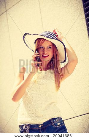 Technology internet social media concept. Young woman wearing sun hat using her smartphone talking to friends. Outdoor shot on sunny summer day