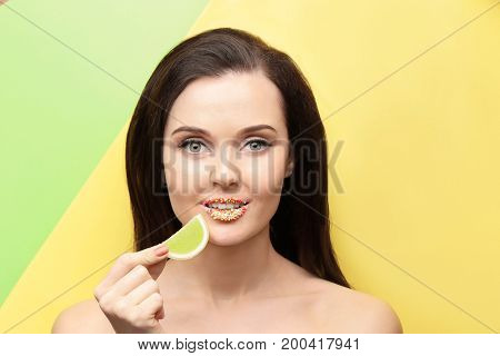 Beautiful young woman with creative makeup and marmalade on color background
