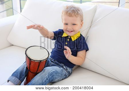 Cute little boy with drum on sofa at home