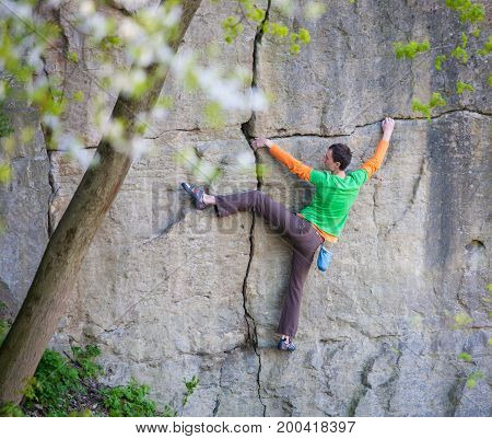 A rock climber on a rock. A man goes in for sports in nature. The strength and endurance of climbers. Climb to the top of the cliff.