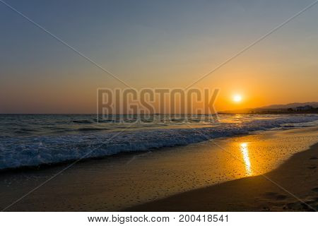 View on a deserted Beach in the warm Light of a beautiful Sunrise. Close-up of long Beach at Sunrise. Beach Background.