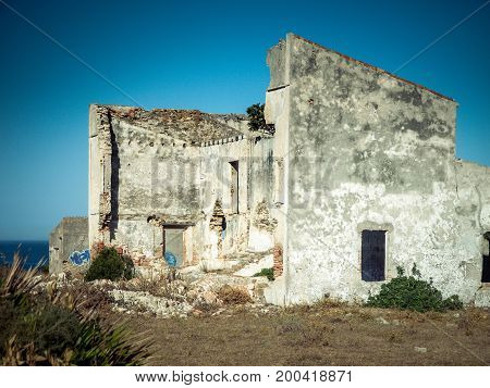 abandoned house ruins with broken walls and blue sky